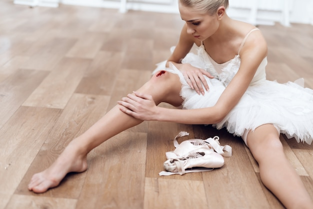 A professional ballerina is sitting on the floor. Premium Photo