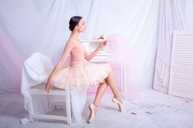 Профессиональная балерина, глядя в зеркало на розовом Бесплатные Фотографии