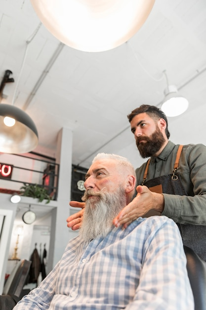 Professional barber finished grooming long gray beard Free Photo
