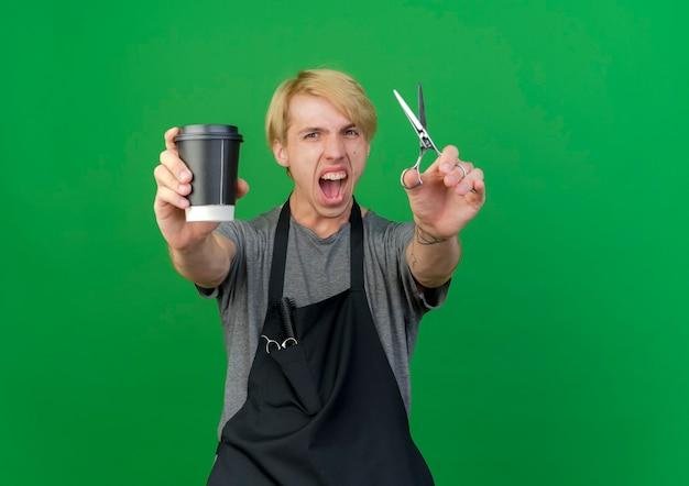 Uomo del barbiere professionista in grembiule che tiene tazza di caffè e forbici che gridano eccitato andando selvaggio Foto Gratuite
