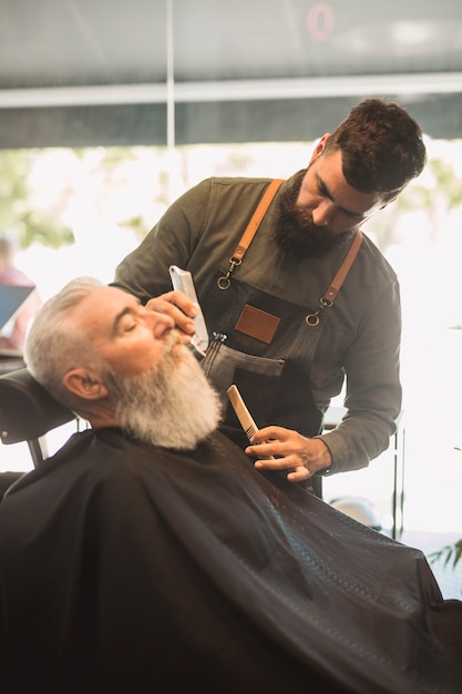 Professional barber with combs and aged bearded male client Free Photo