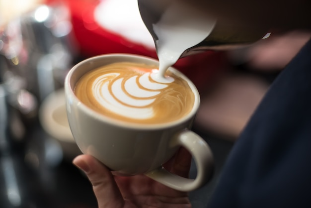 Professional barista pouring milk into the cup of coffee Free Photo