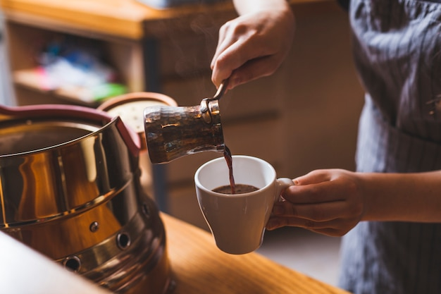 Professional barista serving traditional turkish coffee in cafeteria Free Photo