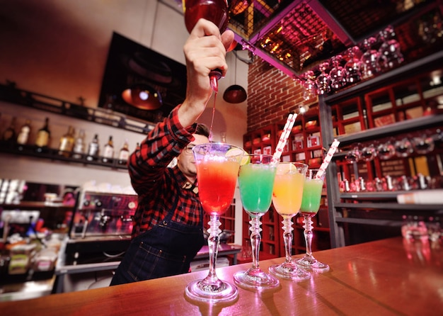Professional bartender prepares and mixes cocktails pouring red syrup from a bottle Premium Photo