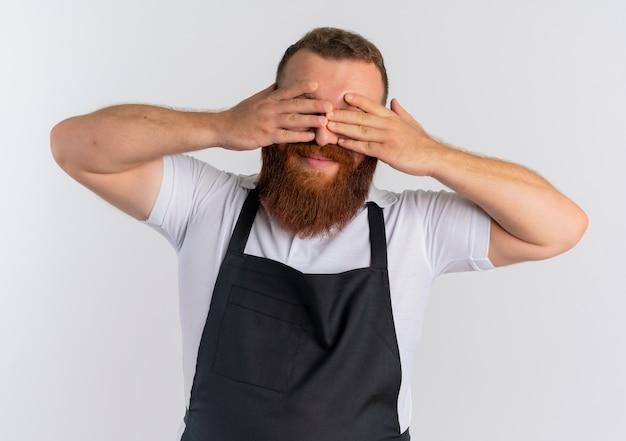 Barbiere barbuto professionista uomo in grembiule sorridente chiudendo gli occhi con le braccia in piedi sopra il muro bianco Foto Gratuite