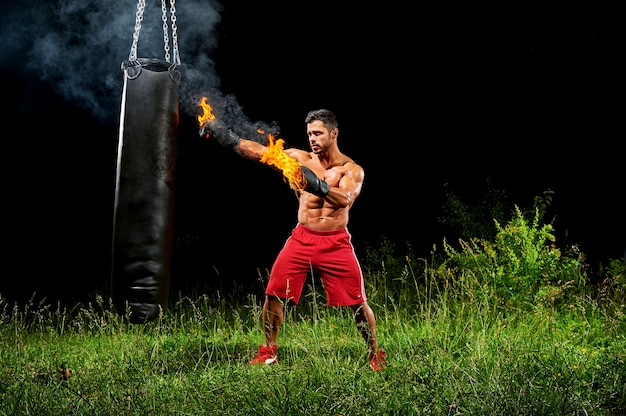 Professional boxer punching sandbag outdoors with his boxing glo Free Photo