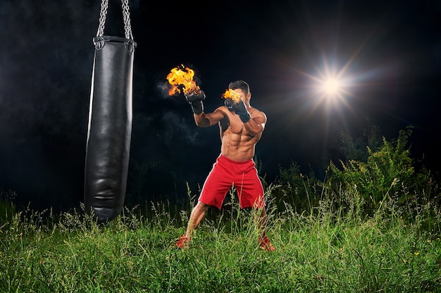 Professional boxer punching sandbag with burning gloves Premium Photo