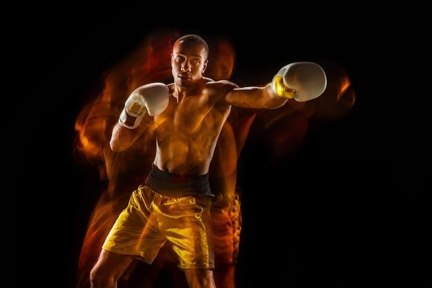 Professional boxer training isolated on black studio background in mixed light Free Photo