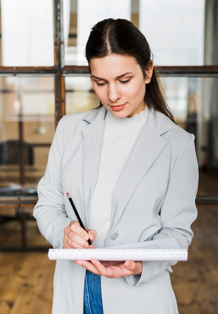 Professional businesswoman writing on diary Free Photo