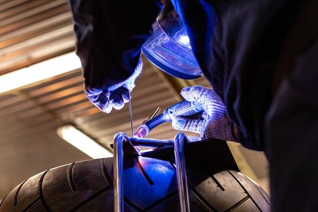 Professional car mechanic working in auto repair service on argon gas cutting machine Premium Photo