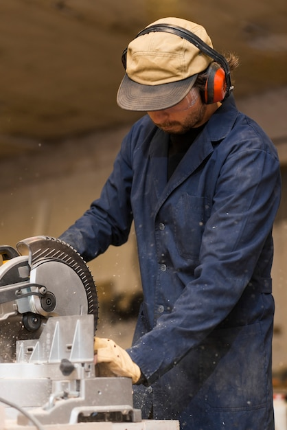 Professional carpenter uses circular saw in workshop Free Photo