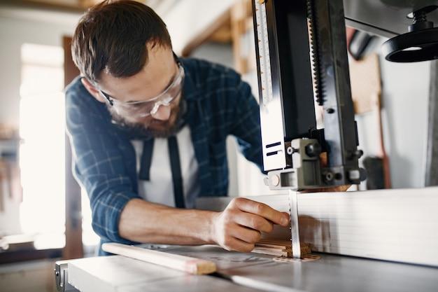 Профессиональный плотник работает с пильной машиной Бесплатные Фотографии
