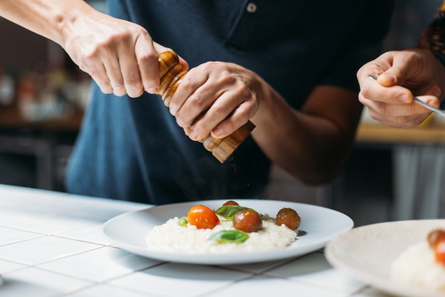 プロのシェフがデザイナーヒップスターキッチンでイタリアのパルメザンリゾットの素晴らしいおいしい蒸し料理を準備します 無料写真