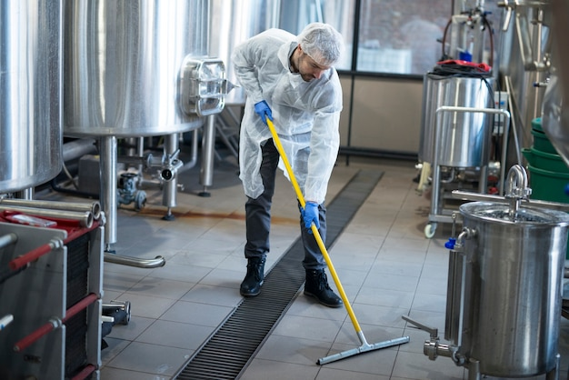 Professional cleaner wearing protection uniform cleaning floor of production plant Free Photo