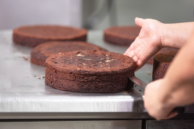 Professional confectioner making a delicious cake in the pastry shop. Premium Photo