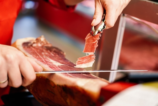 Professional cutter carving slices from a whole bone-in serrano ham Free Photo