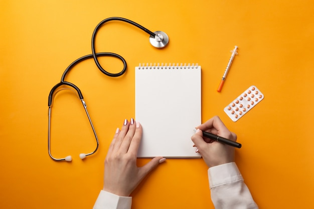 Professional doctor writing medical records in a notebook with stethoscope, syringe and pills Premium Photo