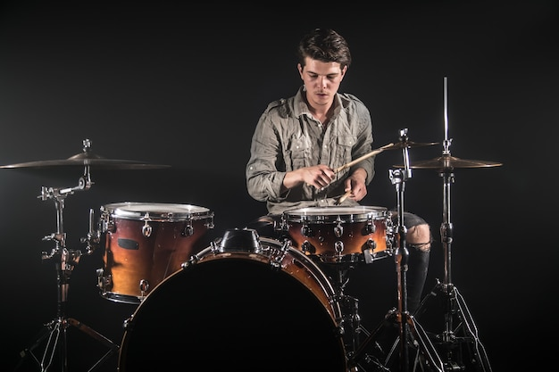 Professional drummer playing on drum set on stage on the black background with drum sticks and vintage look. top view. smoke effect Free Photo