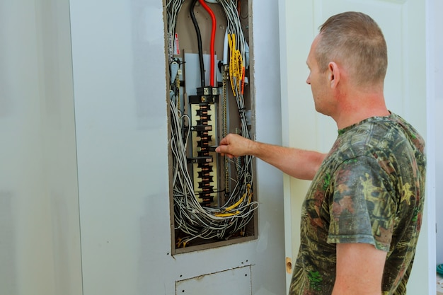 Professional electrician installing components in electrical shield Premium Photo