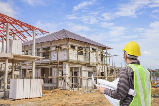 住宅建築建設現場の背景で保護ヘルメットと青写真紙を持つプロのエンジニア建築家労働者 Premium写真