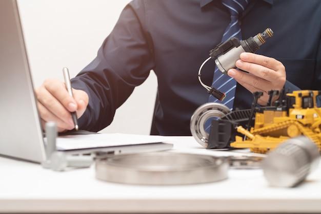 プロフェッショナルエンジニアのインスペックソレノイドバルブおよびオフィスでの作業日のレポート作成;修理メンテナンス重機コンセプト Premium写真
