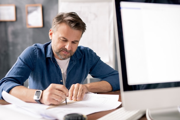 사무실에서 직장으로 새로운 건설의 스케치를 그리는 동안 청사진을 가리키는 연필로 전문 엔지니어 프리미엄 사진