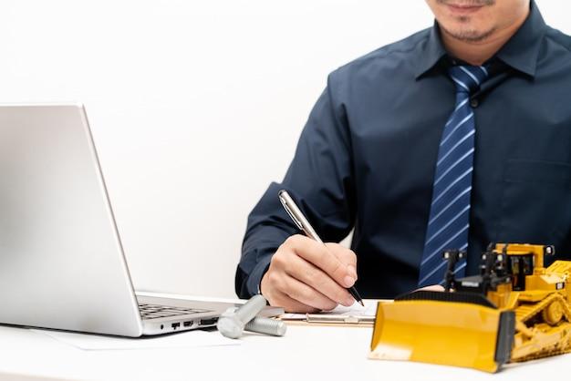 プロのエンジニアがレポートを書いて、オフィスでの作業中に修理メンテナンス重機コンセプト Premium写真
