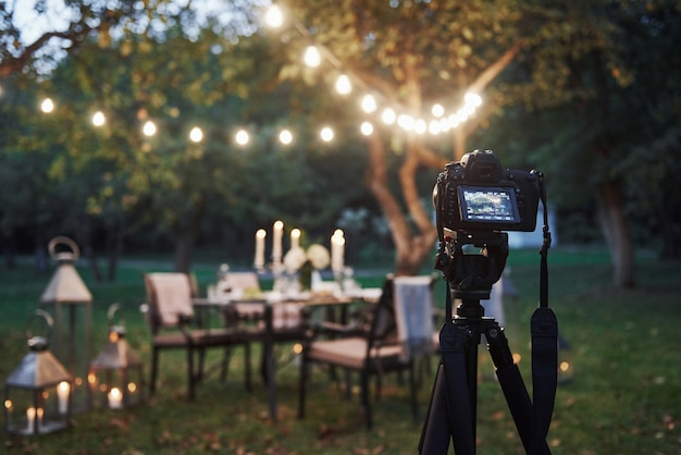 プロフェッショナル機器。夕方には準備されたテーブルの前のフィールドに三脚スタンドのカメラ 無料写真