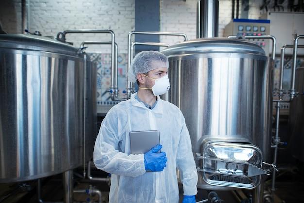 タブレットを保持し、食品製造工場で脇を見ている白い保護ユニフォームの専門の経験豊富な技術者 無料写真