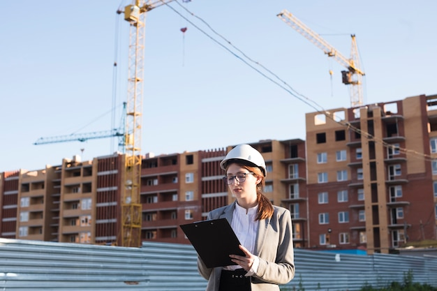 Professional female architecture writing on clipboard at construction site Free Photo