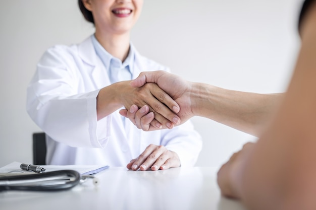 Professional female doctor in white coat shaking hand with patient after successful recommend treatment methods after results about the problem illness, medicine and health care concept Premium Photo