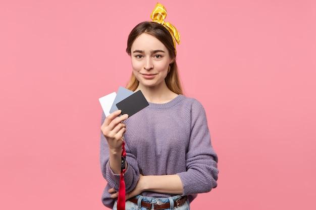 露出とホワイトバランスの設定を調整するために白、グレー、黒のカードを保持しているプロの女性写真家 無料写真