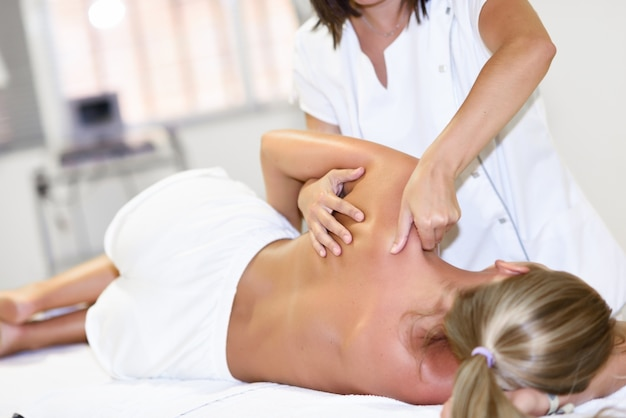 Professional female physiotherapist giving shoulder massage to blonde woman Free Photo