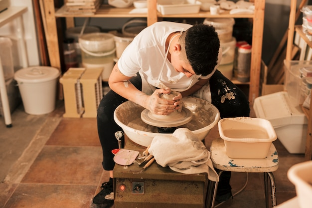 Professional female potter making pot in pottery workshop Free Photo