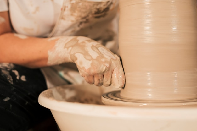 Professional female potter smoothing clay on potter's wheel Free Photo
