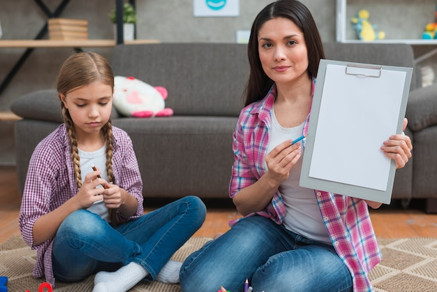 Professional female psychologist sitting with girl on carpet showing white paper on clipboard Free Photo