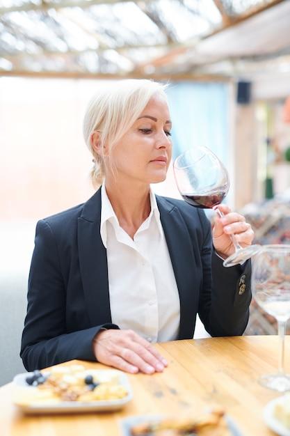 Профессиональная женщина-сомелье сидит за деревянным столом, оценивая запах и вкус красного вина в ресторане Premium Фотографии