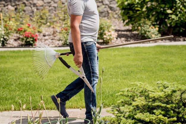 プロの庭師は、庭のはさみと熊手で木を切りに行きます。ランドスケープデザイン。園芸 Premium写真
