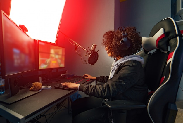 Professional girl gamer plays in video game on her computer. she's participating in online cyber games tournament, plays at home, or in internet cafe. she wears gaming headset Premium Photo