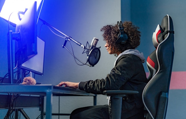 Professional girl gamer plays in video game on her computer. she's participating in online cyber games tournament, plays at home, or in internet cafe. she wears gaming headset. Premium Photo