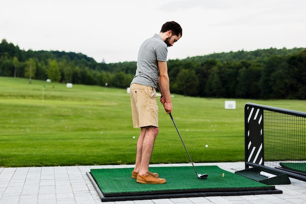 Professional golf player practising on a golf field Free Photo