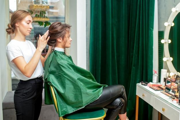 전문 미용사는 미용실에서 여성을위한 헤어 스타일을 만듭니다. 프리미엄 사진