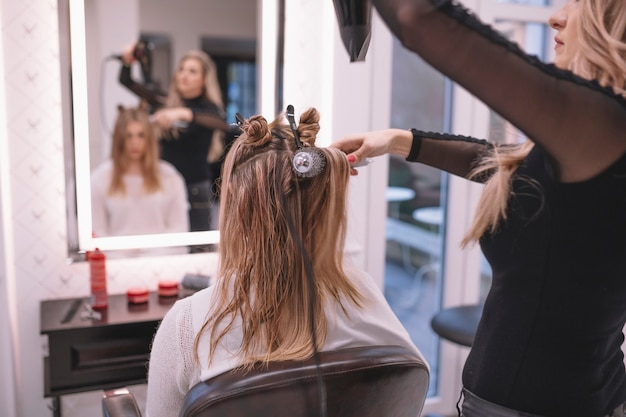 professional hairstylist setting hair of client free photo