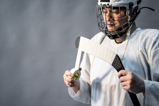 Professional ice hockey player feel angry, one lighting in dark room. Premium Photo