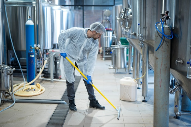 Professional industrial cleaner in protective uniform cleaning floor of food processing plant Free Photo