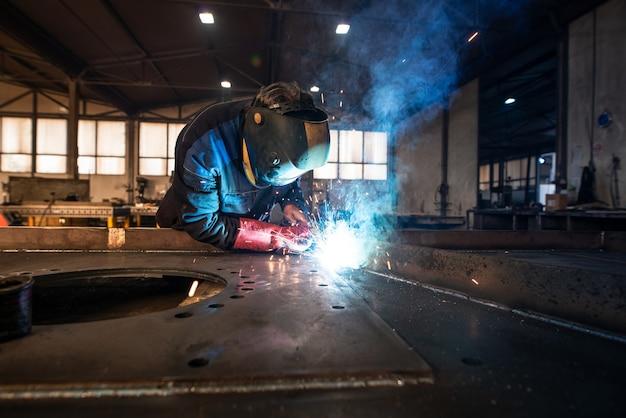 금속 가공 공장에서 금속 부품을 용접하는 전문 산업 용접기 무료 사진