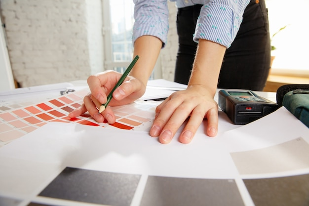 Professional interior designer or architector working with colour palette, room drawings in modern office. Free Photo