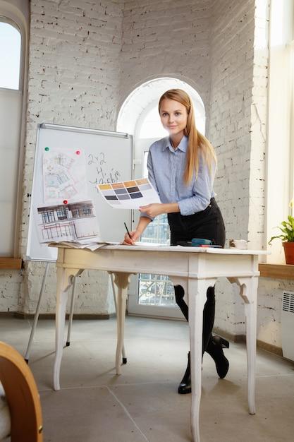 Профессиональный дизайнер интерьера или архитектор, работающий с цветовой палитрой, чертежами помещений в современном офисе. молодая женская модель, планирующая будущую квартиру или дом, выбирая цвета и декорирование. Бесплатные Фотографии