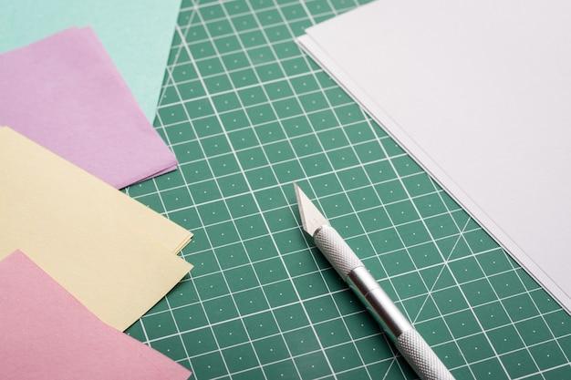 Профессиональный нож рядом с чистой белой бумагой и бумагой разного цвета на коврике Premium Фотографии