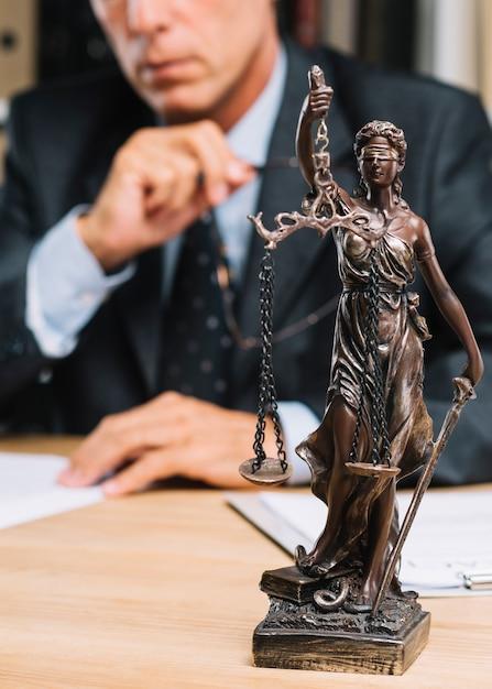 Профессиональный юрист, сидящий за столом со статуей правосудия на переднем крае Premium Фотографии